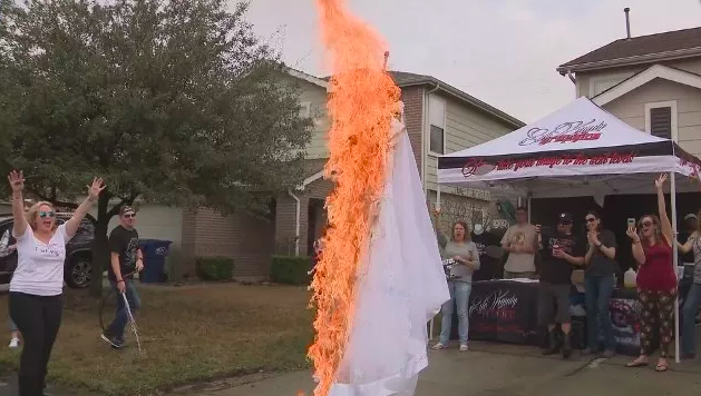 Briana Barksdale torching her wedding dress in front of local TV cameras. (Photo: KMOV)