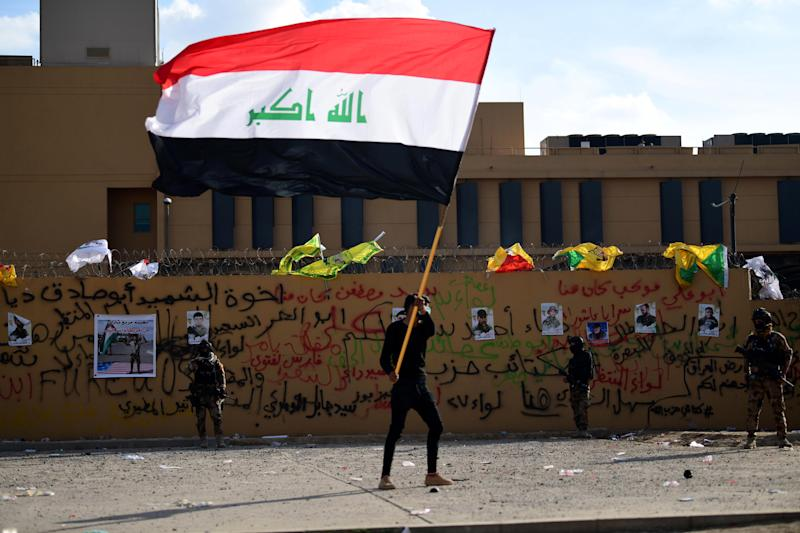 A supporter of Iraqi Shiite armed group popular mobilisation forces carries the Iraqi national flag in front of the US Embassy in Baghdad, Iraq.