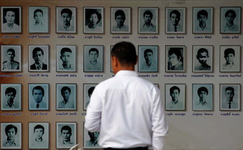 FILE PHOTO: A man looks at portraits of slain pro-democracy activists during a commemoration of a mass uprising against military rule 41 years ago, in Bangkok