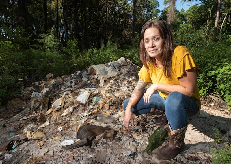 Abbey Rodamaker inspects the trash and garbage that contaminates her property near Gulf Breeze on Wednesday, Oct. 9, 2019. She and her husband bought the six acres of secluded land off of U.S. 98 to build their dream home only to discover it was once used as a landfill.