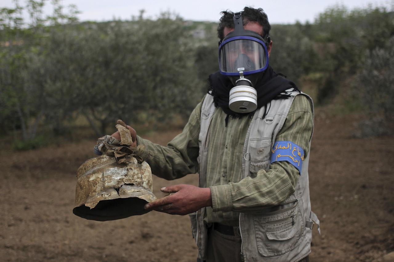 FILE PHOTO: A Civil Defence member carries a damaged canister in Ibleen village from what activists said was a chlorine gas attack, on Kansafra, Ibleen and Josef villages, Idlib countryside, Syria May 3, 2015. REUTERS/Abed Kontar/File Photo To match Special Report MIDEAST-CRISIS/SYRIA-CHEMICALWEAPONS