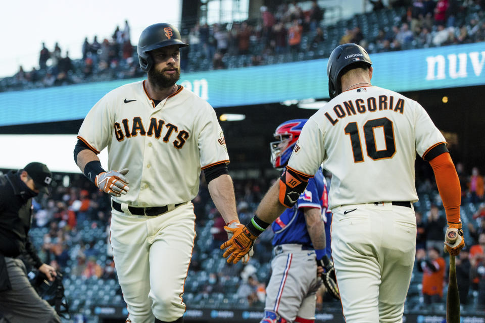 San Francisco Giants' Brandon Belt, left, celebrates with Evan Longoria (10) after hitting a solo home run against the Texas Rangers during the fourth inning of a baseball game in San Francisco, Monday, May 10, 2021. (AP Photo/John Hefti)