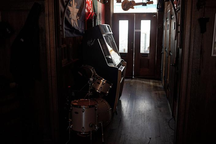 Looking toward a door, from which the sun pours through, a jukebox is seen in the foreground.