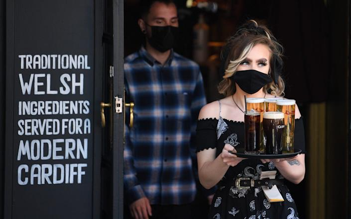 A woman carries a tray of beer at Pitch bar on April 26, 2021 in Cardiff, Wales - Matthew Horwood/Getty Images Europe