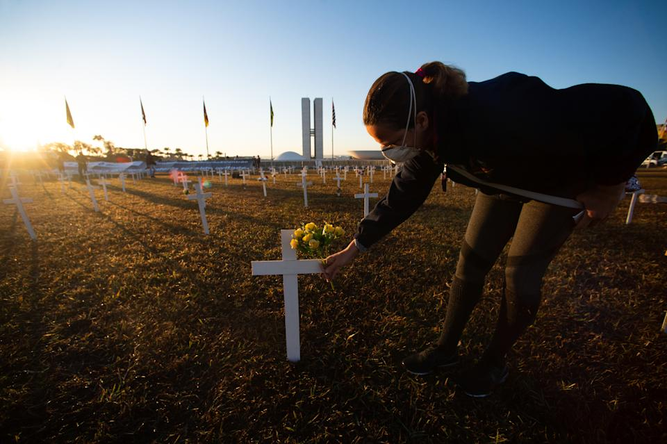 BRASILIA, BRAZIL - JUNE 28: A woman puts a flower on the cross during demonstration in honor of victims of coronavirus (COVID-19) in front Nacional Congress on June 28, 2020 in Brasilia. Brazil has over 1.313,000 confirmed positive cases of Coronavirus and 57,070 deaths. (Photo by Andressa Anholete/Getty Images)