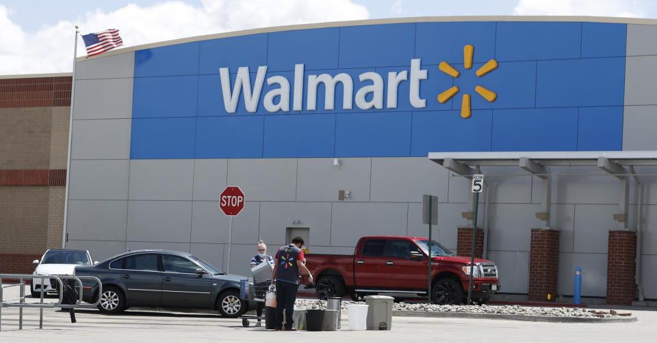 Workers sanitize items outside a Walmart that has been closed following the deaths of three people connected to the store after they were infected with the new coronavirus and at least six more employees have tested positive for COVID-19, Friday, April 24, 2020, in Aurora, Colo. (AP Photo/David Zalubowski)