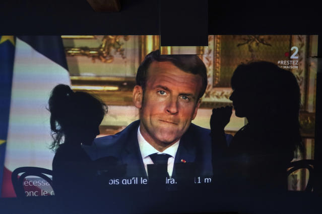A family watches French President Emmanuel Macron's televised speech, Monday April 13, 2020, in Lyon, central France. (AP Photo/Laurent Cipriani)