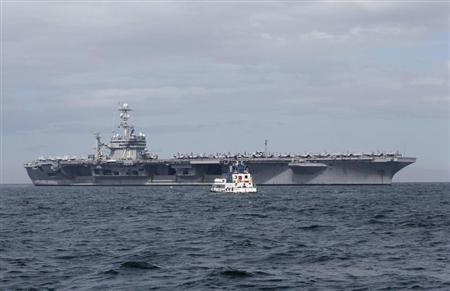 A tugboat approaches the U.S. Navy aircraft carrier George Washington docked after its arrival at a Manila bay