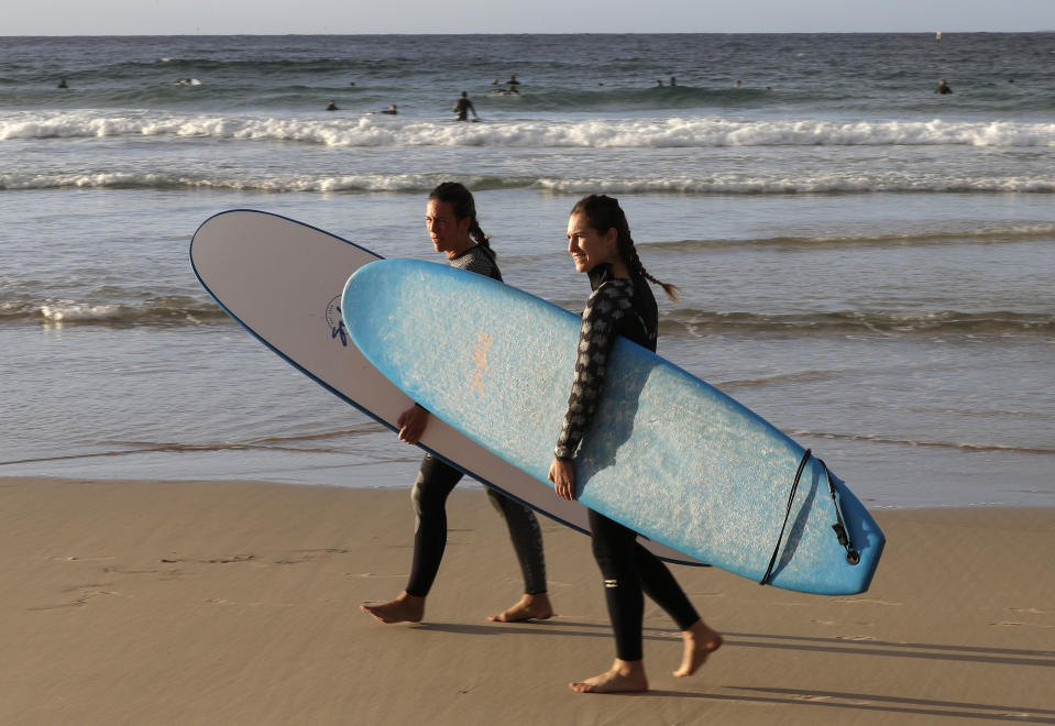 Surfers prepare to enter the water at Bondi Beach in Sydney, Tuesday, April 28, 2020, as coronavirus pandemic restrictions are eased. The beach is open to swimmers and surfers to exercise only. (AP Photo/Rick Rycroft)