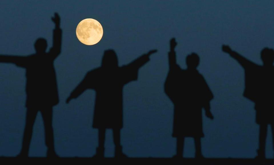 A full moon over The Beatles statues on Penny Lane, Liverpool.