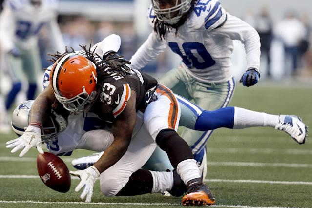 Cleveland Browns running back Trent Richardson (33) loses control of the ball after being tackled by Dallas Cowboys' Gerald Sensabaugh (43) as Danny McCray (40) watches in the second half of an NFL football game, Sunday, Nov. 18, 2012, in Arlington, Texas. Richardson recovered his own fumble on the play. (AP Photo/Sharon Ellman)