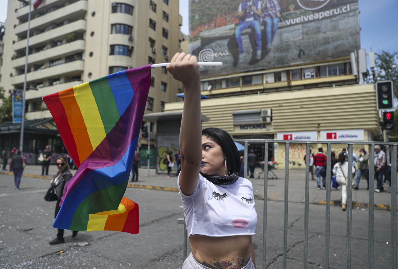 "Pre-school teacher Noemi Gonzalez flies a gay pride flag near La Moneda presidential palace prior a march against Chile's President Sebastian Pinera's government, in Santiago, Chile, Tuesday, Oct. 29, 2019. ""I come to protest because of the dissatisfaction and inequality, because of all of the abuses that the military services have committed, what the 'Carabineros' have done. Rapes of women, murders, 121 disappeared. We are in a democratic country dressed as a democracy but it's really a dictatorship."" Gonzalez said. (AP Photo/Esteban Felix)"
