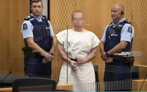 Brenton Tarrant, gestures as he is lead into the dock for his appearance for murder in the Christchurch District Court on March 16, 2019 in Christchurch, New Zealand - Credit: Getty