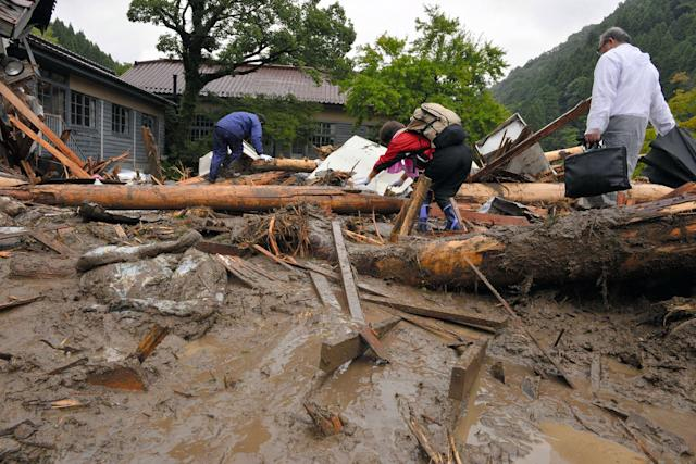 <p>Local residents walk on driftwood blocking the way to their homes as torrential rain hit on July 6, 2017 in Toho, Fukuoka, Japan. T (Photo: The Asahi Shimbun via Getty Images) </p>