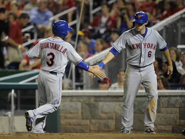 New York Mets' Omar Quintanilla (3) and Matt den Dekker (6) celebrate after they scored on a single by Eric Young Jr. during the third inning of a baseball game against the Washington Nationals, Saturday, Aug. 31, 2013, in Washington. (AP Photo/Nick Wass)