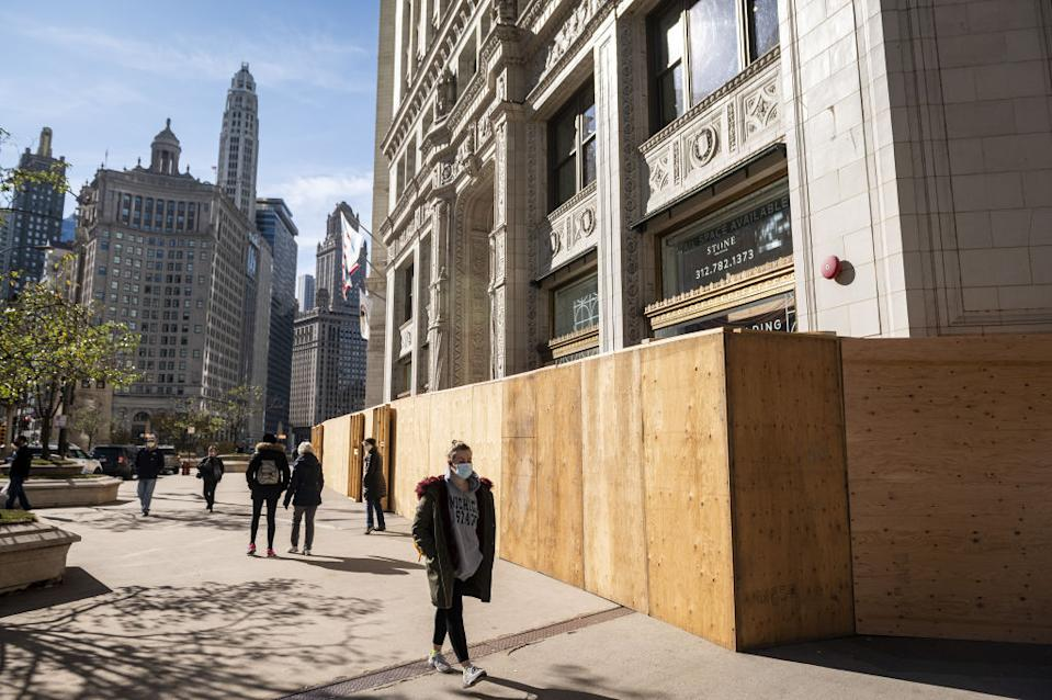 Pedestrians pass in front of a plywood security fence surrounding the Wrigley Building on Michigan Avenue in Chicago.
