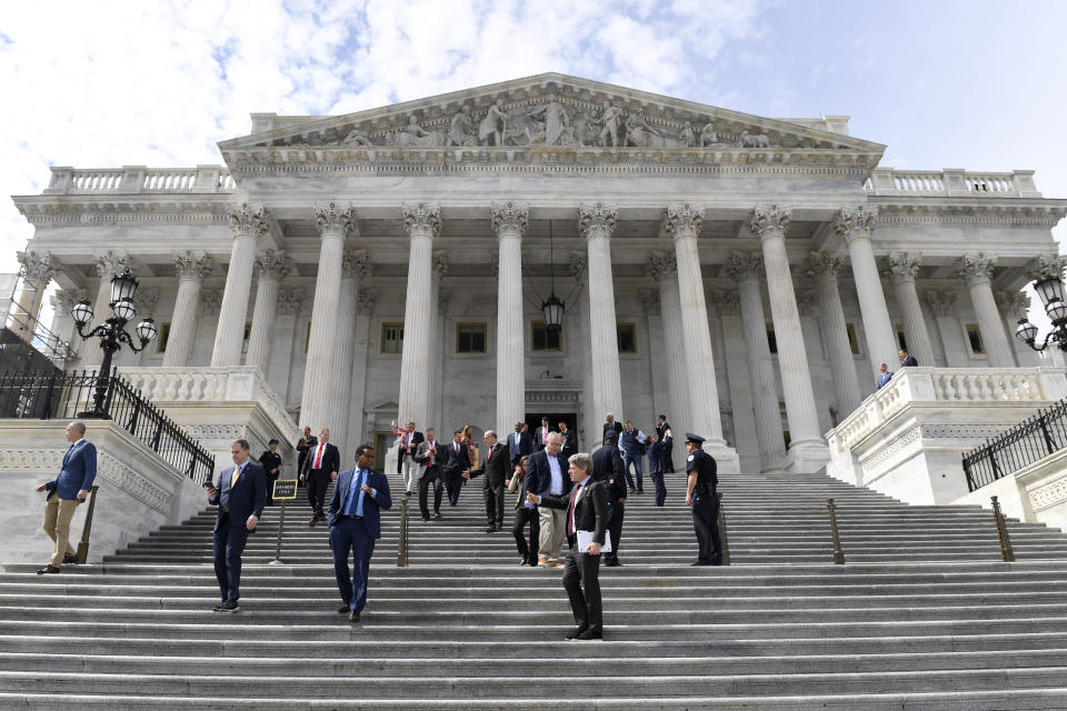 """FILE - In this Friday, March 27, 2020, file photo, members of the House of Representatives walk down the steps of Capitol Hill in Washington after passing a coronavirus rescue package. On Thursday, Dec. 24, 2020, The Associated Press reported on stories circulating online incorrectly asserting that members of Congress gave themselves more than $40,000 in pay raises this year while only giving Americans $1,200 checks and voting to give just $600 more. House Appropriations Committee spokesperson Evan Hollander confirmed to the AP that congressional salaries did not go up this year. """"In fact, the legislation just passed specifically blocks the COLA that would otherwise have taken effect,"""" Hollander said, referring to an automatic """"cost of living adjustment"""" in pay. (AP Photo/Susan Walsh)"""