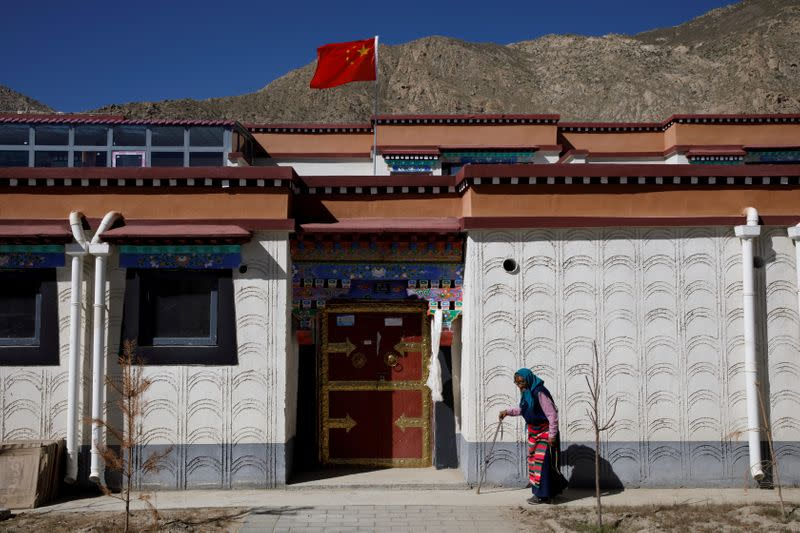 FILE PHOTO: A woman walks in a purpose built village for Tibetans who have been relocated from high-alitude locations in Gongga County