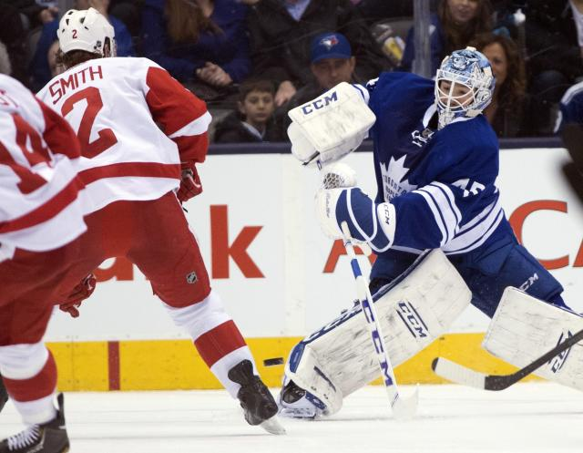 Toronto Maple Leafs goaltender Jonathan Bernier, right, clears the puck under pressure from Detroit Red Wings defenseman Brendan Smith during second-period NHL hockey game action in Toronto, Saturday, March 29, 2014. (AP Photo/The Canadian Press, Frank Gunn)