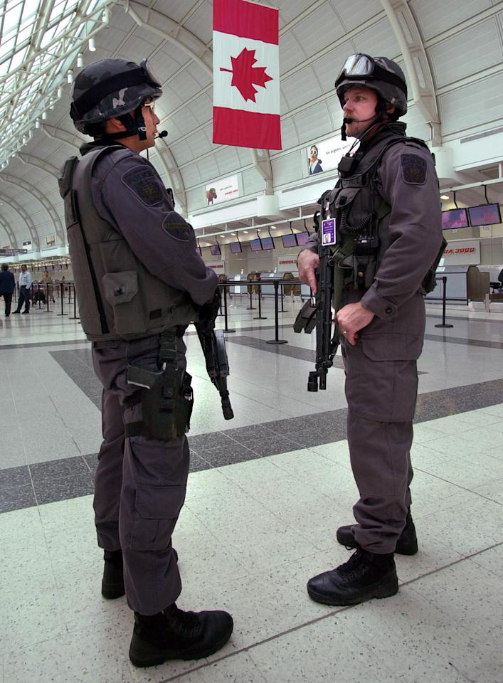 <p>Heavily armed police patrol in Toronto's Pearson International Airport on Sept. 12, 2001 in response to terrorist attacks that took place in the United States on Sept. 11, 2001. Four passenger airliners were highjacked with two flying into the World Trade Center Towers, one flying into the Pentagon and one crashing into a field in rural Pennsylvania. AFP PHOTO/J.P. Moczulski </p>