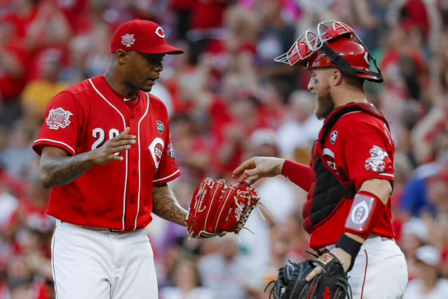 Cincinnati Reds second baseman Christian Colon, left, celebrates with catcher Tucker Barnhart, right, after closing the ninth inning of a baseball game against the New York Mets, Saturday, Sept. 21, 2019, in Cincinnati. (AP Photo/John Minchillo)