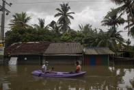 Sri Lankans ride a raft in an inundated street following heavy rainfall at Malwana, on the out skirts of Colombo, Sri Lanka, Saturday, June 5, 2021. Flash floods and mudslides triggered by heavy rains in Sri Lanka have killed at least four people and left seven missing, while more than 5,000 are displaced, officials said Saturday. Rains have been pounding six districts of the Indian Ocean island nation since Thursday night, and many houses, paddy fields and roads have been inundated, blocking traffic. (AP Photo/Eranga Jayawardena)