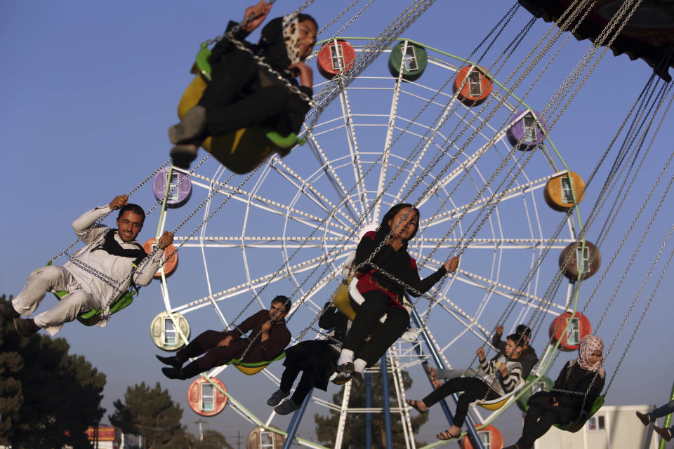FILE - In this Nov. 14, 2014 file photo, visitors ride a ferris wheel at Afghanistan's first amusement park called City Park, in Kabul. The Taliban fighters who rolled into Afghanistan's capital and other cities in recent days appear awestruck by the towering apartment blocks, modern office buildings and shopping malls. When the Taliban last seized power, in 1996, the country had been ravaged by civil war and the capital was in ruins. (AP Photo/Rahmat Gul, File)