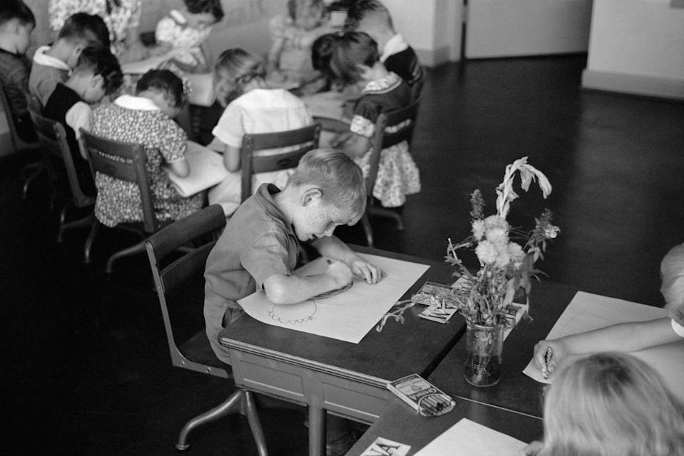 <p>A young boy works at his desk at a school located in a Greenbelt Community in Ohio, which was constructed as a part of President Franklin D. Roosevelt's New Deal. </p>