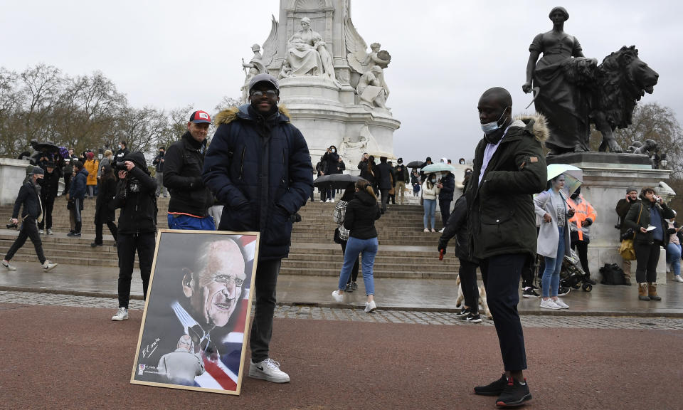 A man stands with an artwork depicting Britain's Prince Philip outside Buckingham Palace in London, a day after the death of Britain's Prince Philip, Saturday, April 10, 2021. Britain's Prince Philip, the irascible and tough-minded husband of Queen Elizabeth II who spent more than seven decades supporting his wife in a role that mostly defined his life, died on Friday. (AP Photo/Alberto Pezzali)