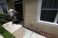 A protesters kicks the door of the Florida home of former Minneapolis police officer Derek Chauvin, in Orlando