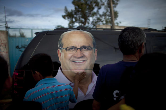 In this photo taken on Thursday, June 21, 2012, a boy passes his hand over an image of Graco Ramirez, the gubernatorial candidate for the Democratic Revolution Party, PRD, displayed on the van that drives away Ramirez, at the end of a political rally in Temixco, on the outskirts of Cuernavaca, Mexico. As Mexicans head to the ballot box Sunday, drug cartels are registering their votes with scare tactics and cold, hard cash to make sure whoever is elected doesn't interfere with their lucrative operations. Ramirez says people in remote areas are telling him that gangs are threatening them to stay home on election day. He complains that gunmen approach his campaign staffers while they are out distributing flyers. (AP Photo/Alexandre Meneghini)