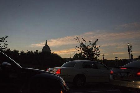 Cars wait at a traffic light as the sun rises over the U.S. Capitol dome in Washington, October 18, 2013. REUTERS/Jonathan Ernst