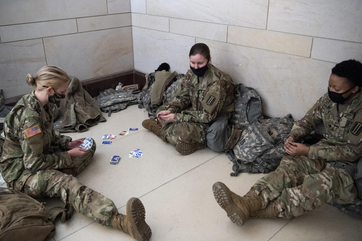Members of the National Guard play cards in the Capitol Visitors Center as the House of Representatives votes on the impeachment of President Donald Trump. (Caroline Brehman/CQ-Roll Call, Inc via Getty Images)