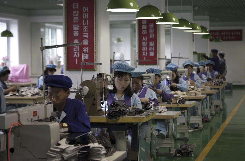 FILE - In this June 22, 2016, file photo, factory workers operate sewing machines at a shoe factory in Wonsan, North Korea. Two months after he failed to win a badly needed easing of sanctions from U.S. President Donald Trump, North Korean leader Kim Jong Un is traveling to Russia in a possible attempt to win its help as the U.S.-led trade sanctions hurt his country's already-struggling economy. (AP Photo/Wong Maye-E, File)