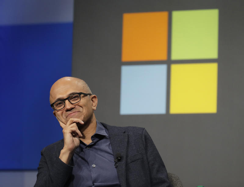 FILE- In this Wednesday, Nov. 28, 2018, file photo Microsoft CEO Satya Nadella listens to a question as he sits in front of the Windows logo during the annual Microsoft Corp. shareholders meeting in Bellevue, Wash. Microsoft on Friday, Nov. 30, surpassed Apple as the world's most valuable publicly traded company. Under Nadella Microsoft has found stability by moving away from its flagship Windows operating system and focusing on cloud-computing services with long-term business contracts. (AP Photo/Ted S. Warren, File)
