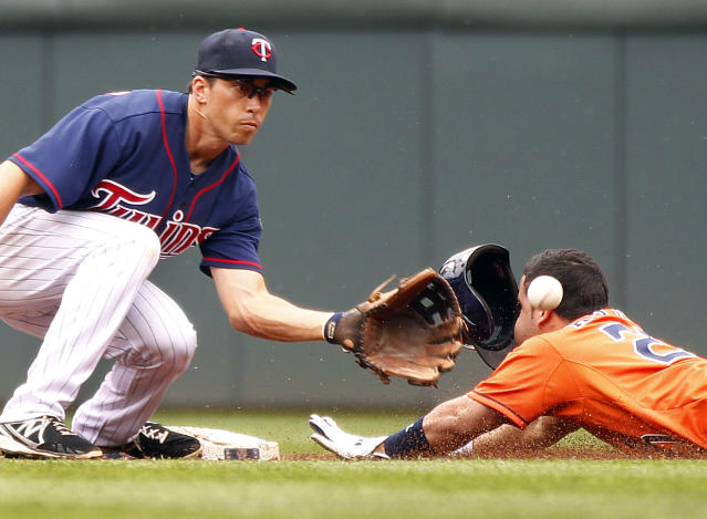 Minnesota Twins shortstop Doug Bernier makes a catch but Houston Astros Jose Altuve slides safely on a steal to second base in the third inning of their baseball game in Minneapolis, Sunday, Aug. 4, 2013.(AP Photo/Andy Clayton-King)