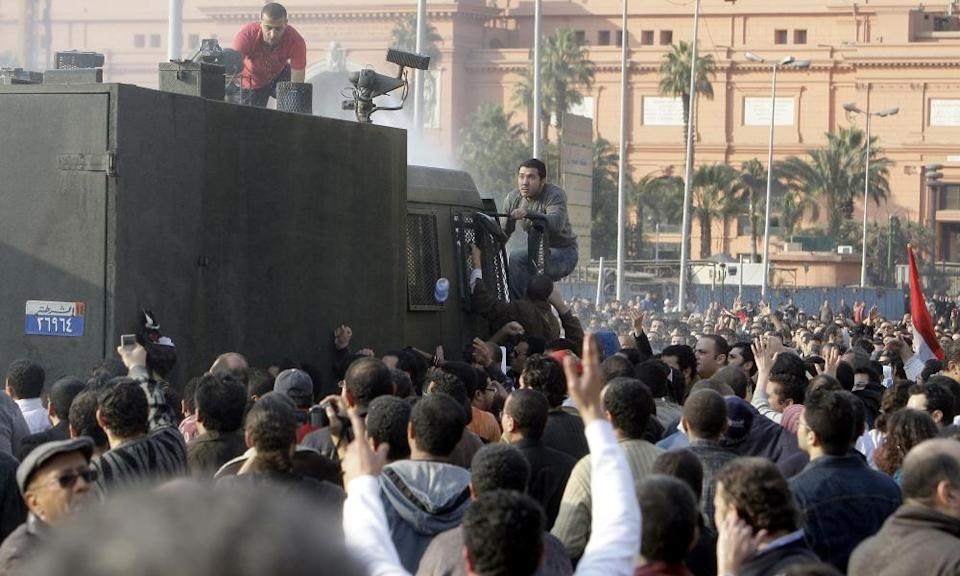 Protesters climb on to a water cannon during a anti-government protest on 25 January 2011.