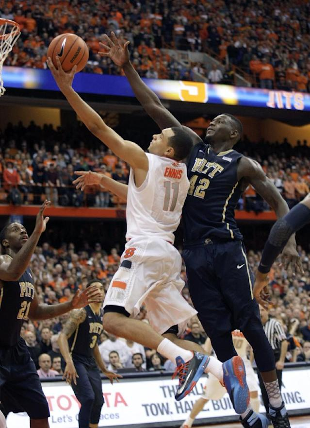Syracuse's Tyler Ennis (11) shoots as Pittsburgh's Talib Zanna, right, defends during the second half of an NCAA college basketball game in Syracuse, N.Y., Saturday, Jan. 18, 2014. Syracuse won 59-54. (AP Photo/Nick Lisi)