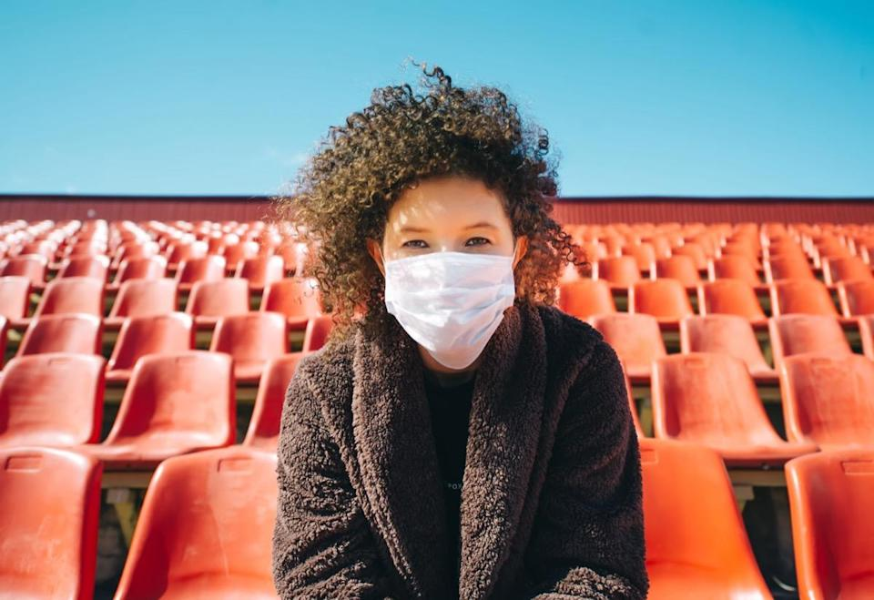 Woman in a surgical mask sitting in an empty stadium.