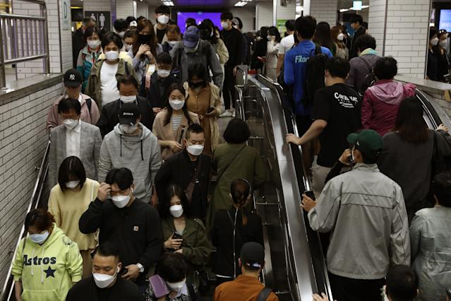 South Korean commuters wear protective masks as they crowd on an escalator and stairs after getting off the subway during rush hour. (Chung Sung-Jun/Getty Images)