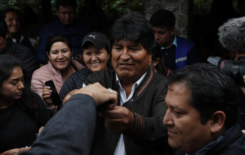 Bolivia's President Evo Morales, center, greets supporters during a visit to a trout farm where he stopped to eat, in Incachaca, Bolivia, Saturday, Oct. 19, 2019. Morales is seeking a fourth term in Sunday's general elections. (AP Photo/Juan Karita)