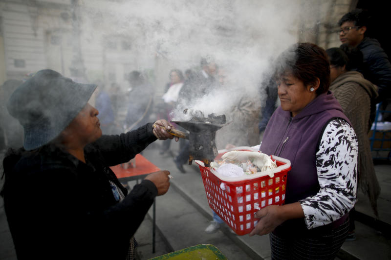In this picture taken Monday, Jan. 6, 2020, spiritual indigenous guide Josefa Oblitas blesses a woman's baby Jesus doll outside the San Francisco Church during the Three Kings Day celebrations in La Paz, Bolivia. Oblitas was among several spiritual guides who performed traditional indigenous blessings outside the church. (AP Photo/Natacha Pisarenko)