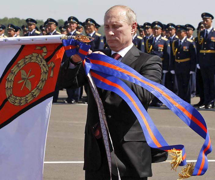 Russian President Vladimir Putin attaches a Russian military medal to an air regiment banner during an award ceremony at a military airbase in the city of Korenovsk, about 1200 kilometers (750 miles) south of Moscow, Thursday, June 14, 2012. President Vladimir Putin says Russia needs a new strategic bomber and will develop it despite high costs. Speaking Thursday at a meeting with the military top brass after visiting a base in southern Russia, Putin said the project would be expensive and technologically challenging. He added that the job needs to be done despite high costs, according to Russian news agencies. (AP Photo/RIA-Novosti, Mikhail Klimentyev, Presidential Press Service)