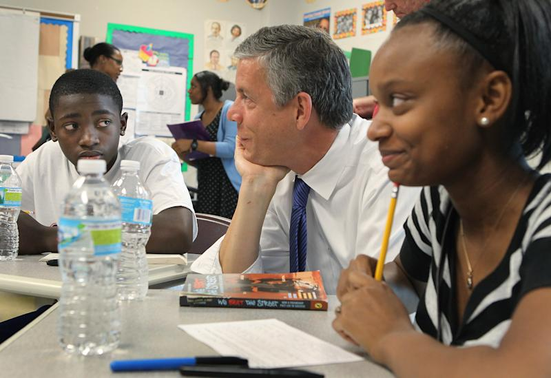 FILE - In this Monday, June 25, 2012 file photo, during a fact-finding tour of Vashon High School, U.S. Secretary of Education Arne Duncan, center, listens to eighth-grade students Delvion Mitchell, 14, and Makayla Lewis, 14, as they discuss social issues they have encountered at school and what they have learned from them, in St. Louis. Five more states have been granted relief from key requirements of the Bush-era No Child Left Behind law, bringing the total to 24 states given waivers, the Education Department said Friday, June 29, 2012. Arkansas, Missouri, South Dakota, Utah and Virginia will be freed from the No Child Left Behind requirement that all students test proficient in math and science by 2014, a goal the nation remains far from achieving. (AP Photo/St. Louis Post-Dispatch, J.B. Forbes, File) EDWARDSVILLE INTELLIGENCER OUT; THE ALTON TELEGRAPH OUT