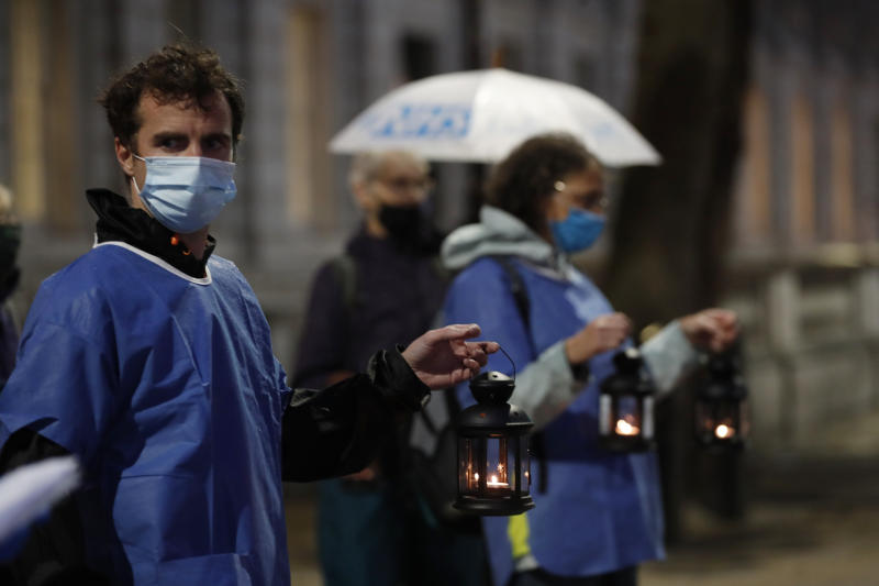 Campaigners hold lanterns outside Downing Street for British NHS medical and care workers who have died due to COVID-19, in London, Friday, July 3, 2020. A number of NHS staff and campaigners carried one lantern to represent people who have died due to COVID-19, as they walked from St. Thomas' Hospital over Westminster Bridge to then hold a candlelit vigil outside Downing Street, where they read out a small number of representative names of NHS staff who died. (AP Photo/Alastair Grant)