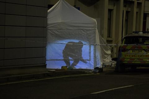 A forensic officer's silhouette is seen through a tent at the scene of a stabbing - Credit: SWNS.com