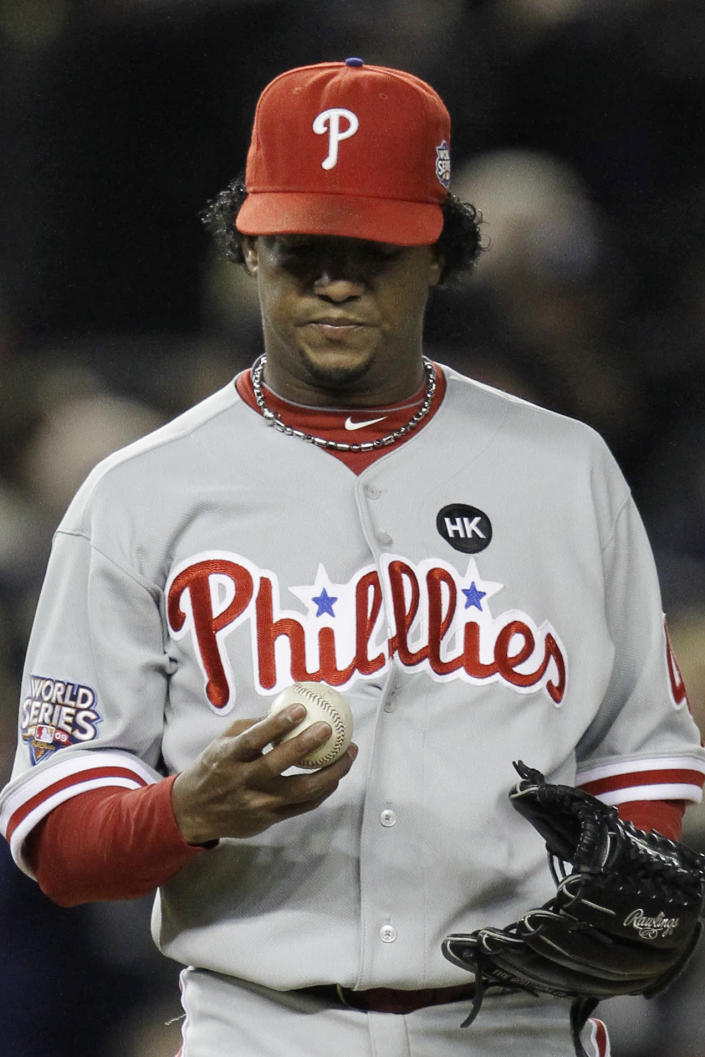 FILE - In this Nov. 4, 2009, file photo, Philadelphia Phillies' Pedro Martinez looks at his ball after giving up a two-run home run to New York Yankees' Hideki Matsui during the second inning of Game 6 of the Major League Baseball World Series in New York. The Phillies lost to the New York Yankees in six games and Martinez went 0-2 in two starts against the Yankees with a 6.30 ERA _ but has long said he was sick in his Game 6 start at Yankee Stadium and always wished he could have that one back. (AP Photo/David J. Phillip, File)