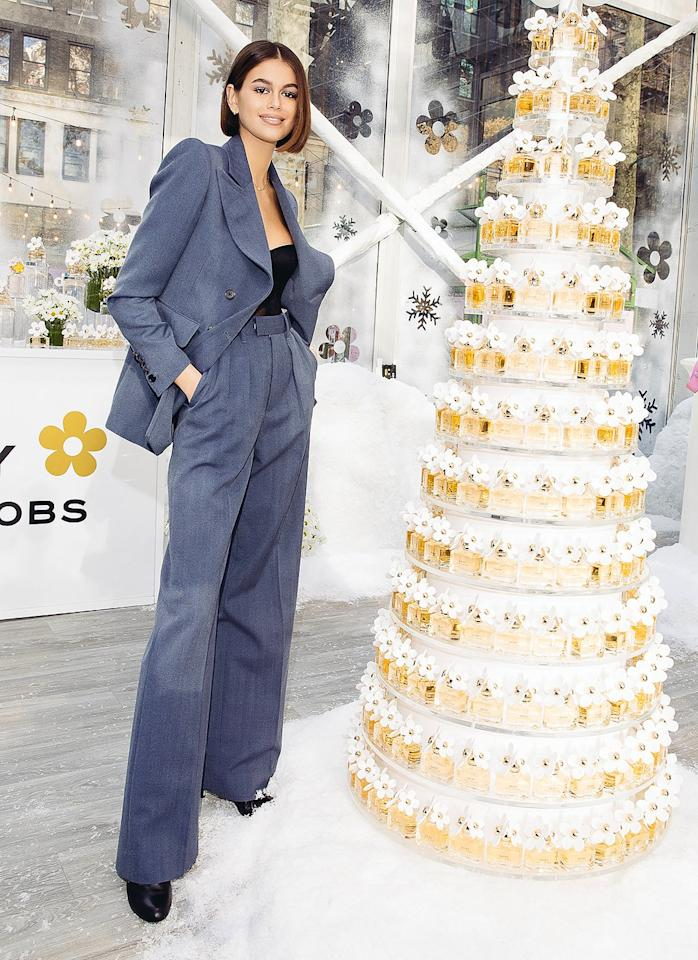 in a charcoal gray suit jacket, matching high-waisted trousers, a black bustier top and black boots at the Daisy Marc Jacobs launch event in N.Y.C.