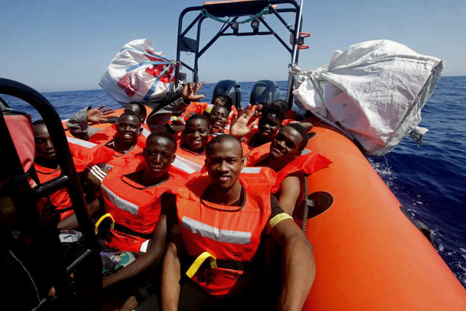 African migrants wave after being rescued by the MV Geo Barents vessel of MSF (Doctors Without Borders), off Libya in the central Mediterranean route, Monday, Sept. 20, 2021. (AP Photo/Ahmed Hatem)