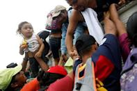Honduran migrants, part of a caravan trying to reach the U.S., go up for a truck during a new leg of their travel in Zacapa, Guatemala October 17, 2018. REUTERS/Edgard Garrido